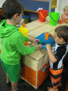 2 young boys play with building blocks and toys